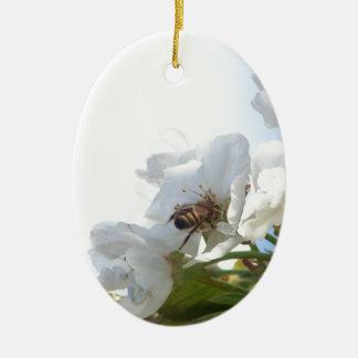 Abeja de la miel en las flores de cerezo adorno ovalado de cerámica