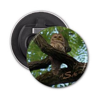 Abrebotellas Un búho barrado en una rama en las maderas