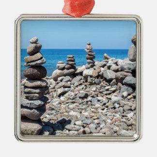 Adorno Metálico Piedras apiladas de la playa en el mar azul