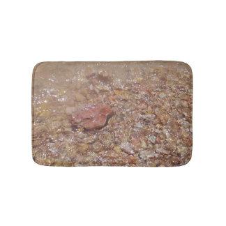 Agua clara sobre piedras alfombrilla de baño