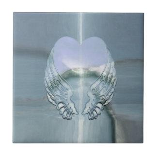 Alas de plata del ángel envueltas alrededor de un azulejo cuadrado pequeño