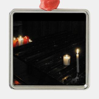 Algunas velas religiosas en una ayuda negra adorno navideño cuadrado de metal