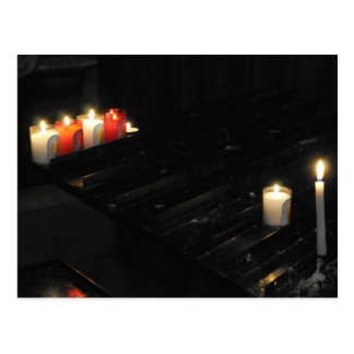 Algunas velas religiosas en una ayuda negra en un postal