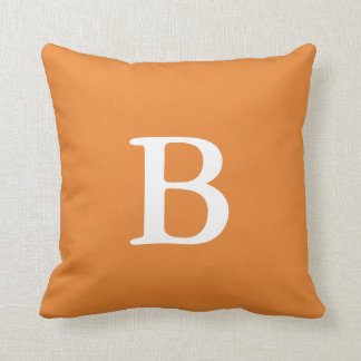 Almohada de tiro anaranjada del monograma