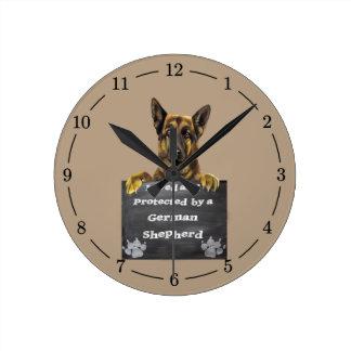 Amado y protegido por un pastor alemán reloj redondo mediano
