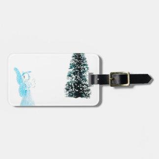 Ángel de cristal azul que ruega cerca del árbol de etiqueta para maletas