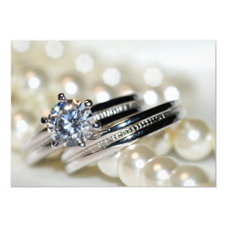 Anillos y perlas blancas que casan la invitación