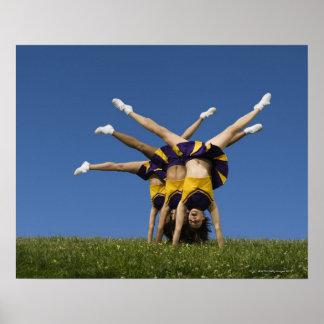Animadoras femeninas que hacen handstands poster