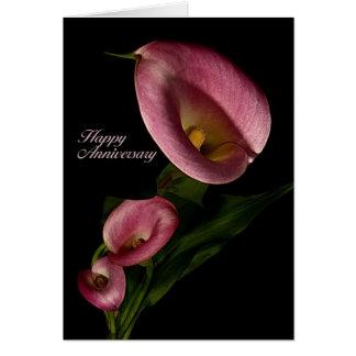 Aniversario feliz con la tarjeta rosada de la cala