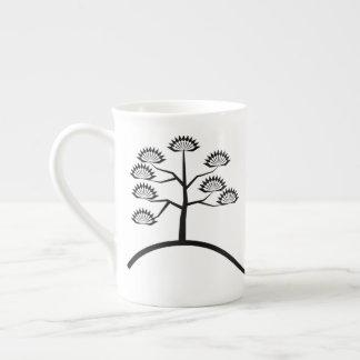 Árbol con la taza negra básica de la porcelana de