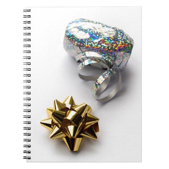 Arco brillante del papel de regalo y cuaderno