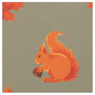 Ardilla roja linda con las hojas de la castaña y tela