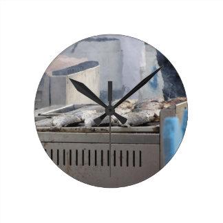 Asando a la parrilla pescados al aire libre con el reloj redondo mediano