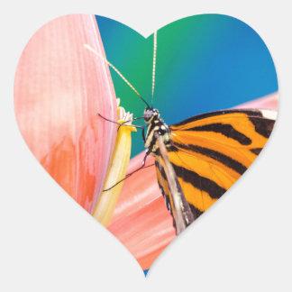 Aterrizaje de la mariposa en la flor púrpura pegatina en forma de corazón