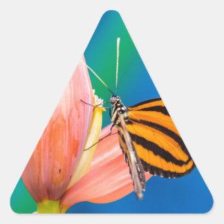 Aterrizaje de la mariposa en la flor púrpura pegatina triangular