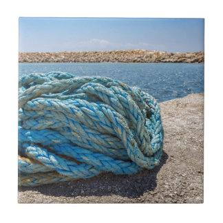 Azulejo Cuerda azul en espiral del amarre en el agua en la