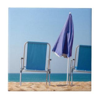 Azulejo De Cerámica Dos sillas y parasoles azules de playa en sea.JPG