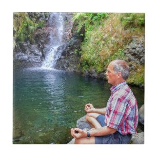 Azulejo De Cerámica Hombre que se sienta en la roca meditating cerca