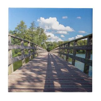 Azulejo De Cerámica Puente de madera largo sobre el agua de la charca