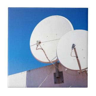 Azulejo Dos antenas parabólicas blancas en la pared de la