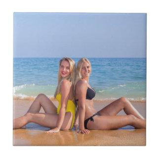 Azulejo Dos chicas se sientan en la playa cerca de sea.JPG