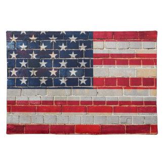 Bandera de América en una pared de ladrillo Salvamanteles