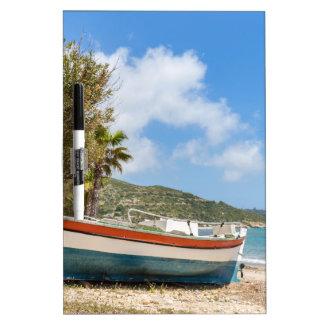Barco colorido que miente en la playa griega pizarra blanca