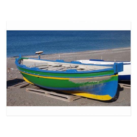 Barco de pesca verde viejo en la playa postal
