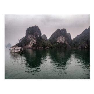 Barco en las islas brumosas de la roca de la bahía postal