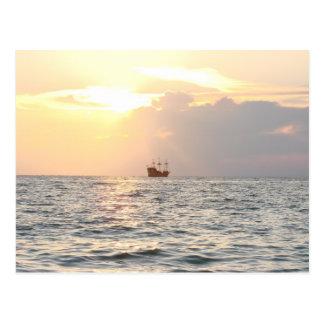 Barco pirata en puesta del sol postal