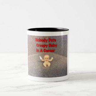 Bebé espeluznante en una taza de cerámica de la