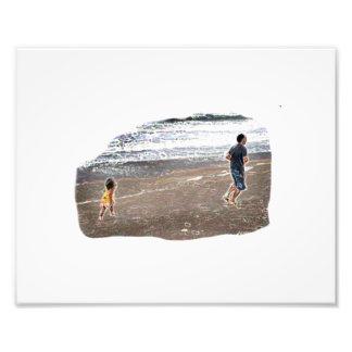 Bebé que persigue al hombre en arte de la playa impresiones fotograficas