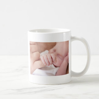 bebé recién nacido que sostiene el dedo de los taza de café