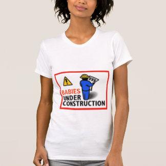 Bebés debajo de la camiseta de la construcción