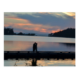 Beso en la puesta del sol postal