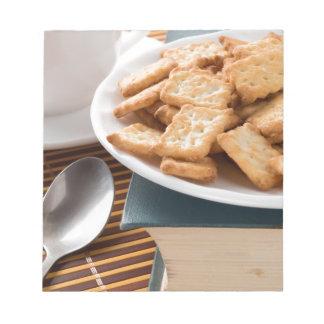 Bloc De Notas Placa blanca con las galletas en el libro viejo