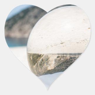 Bola de cristal en la playa griega arenosa pegatina en forma de corazón