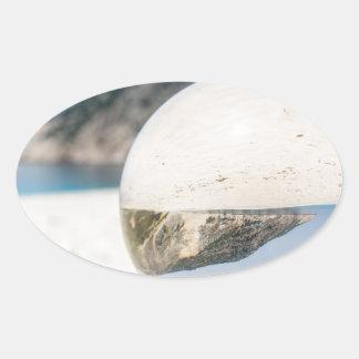 Bola de cristal en la playa griega arenosa pegatina ovalada