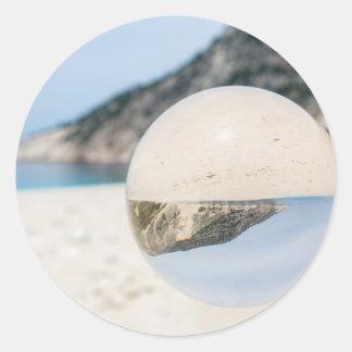 Bola de cristal en la playa griega arenosa pegatina redonda