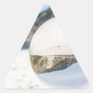 Bola de cristal en la playa griega arenosa pegatina triangular