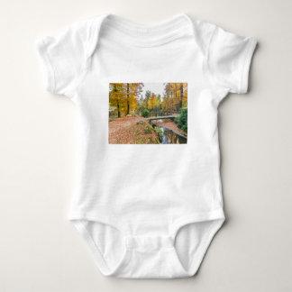 Bosque con la charca y puente en colores de la body para bebé