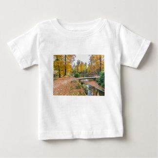 Bosque con la charca y puente en colores de la camiseta de bebé