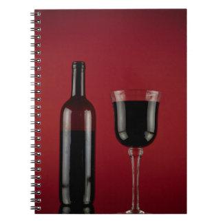 Botella de cristal del rojo de vino cuaderno