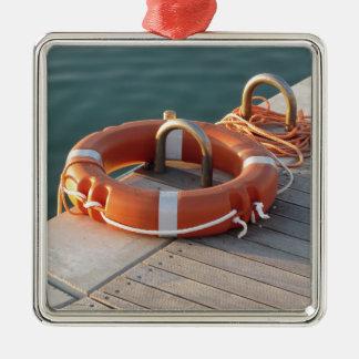 Boya de vida anaranjada en el embarcadero de adorno navideño cuadrado de metal