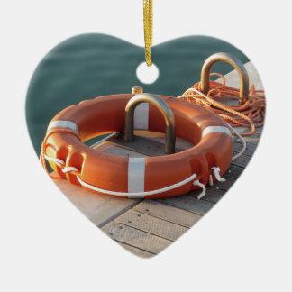 Boya de vida anaranjada en el embarcadero de adorno navideño de cerámica en forma de corazón