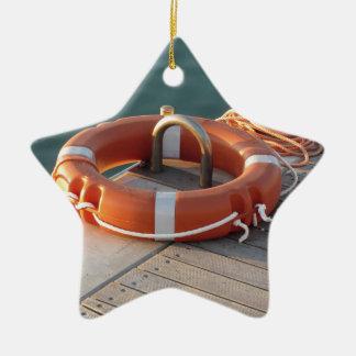 Boya de vida anaranjada en el embarcadero de adorno navideño de cerámica en forma de estrella