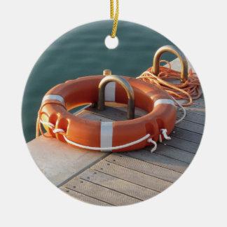Boya de vida anaranjada en el embarcadero de adorno navideño redondo de cerámica