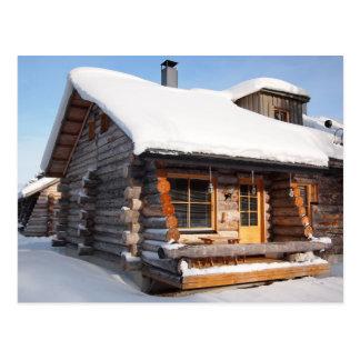 Cabaña de madera nevada en la postal de Laponia
