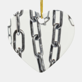 Cadenas que cuelgan delante del fondo blanco adorno navideño de cerámica en forma de corazón
