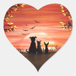 Caída del perro y del gato de la puesta del sol pegatina en forma de corazón